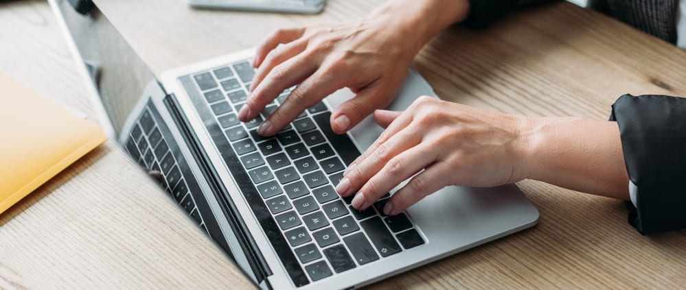 Older woman's hands on keyboard, aging hands
